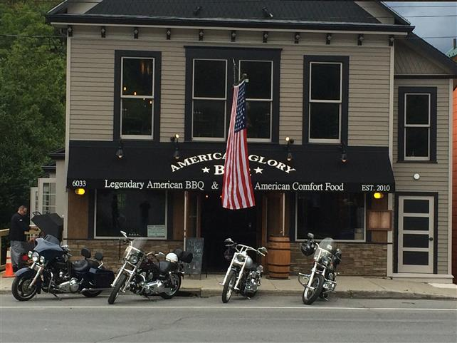 Storefront view from road. Black awning printed with American Glory B B Q. Legendary american B B Q. American comfort food. Building is brick and vinyl siding. Four motorcycles parked in front.