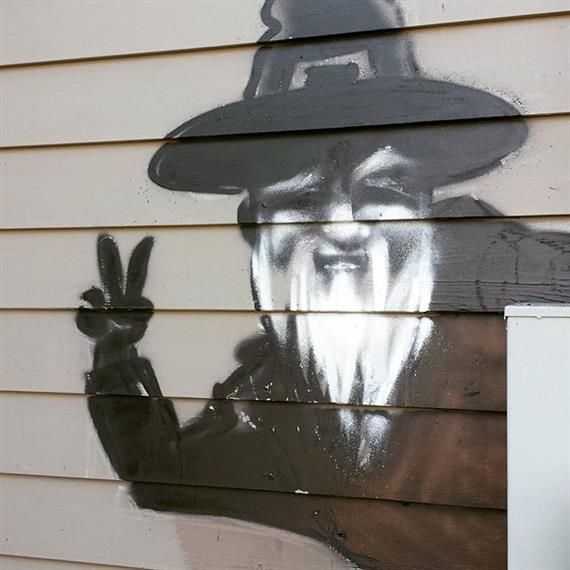 Graffiti art on exterior of building showing man with gray beard and buckled hat giving peace sign.