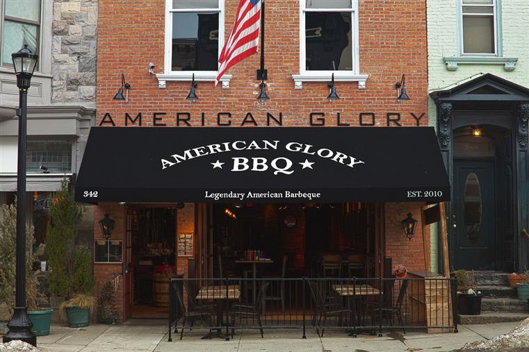 Storefront from road. American Glory B B Q printed on black awning. American glory letters above on brick of building. Outdoor seating is shown.