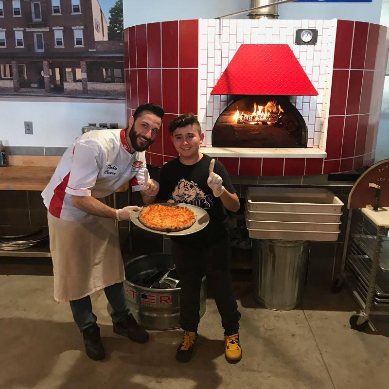 Man and child posing for picture infront of a wood burning oven