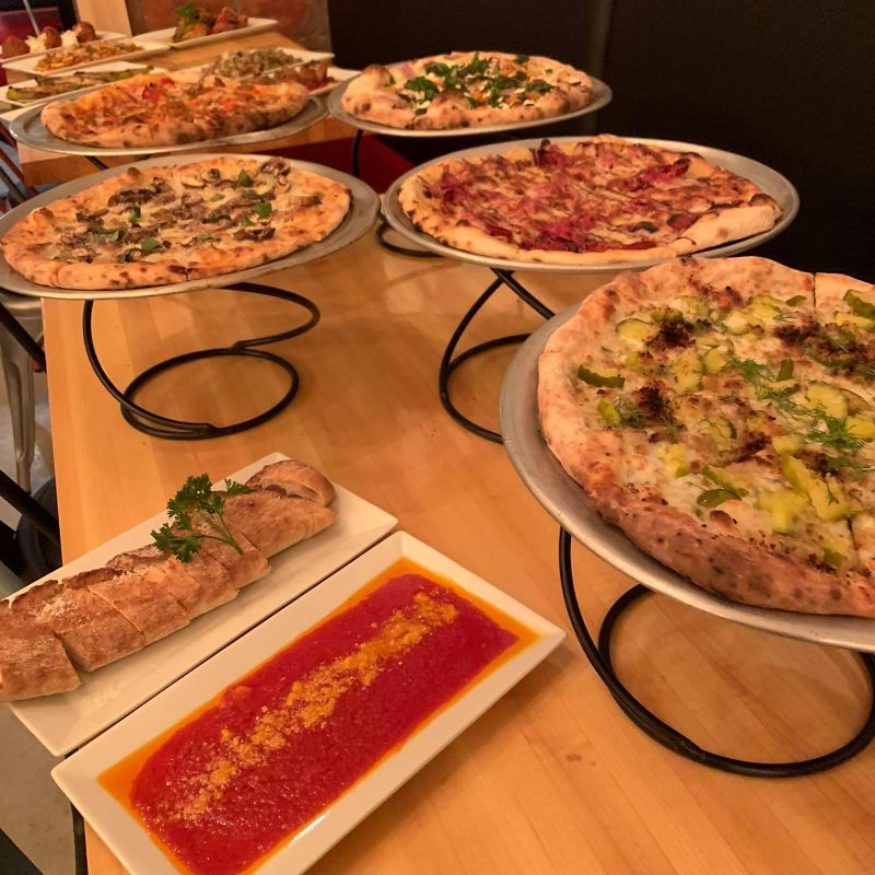 Variety of pizzas on a wooden table with sauce on side