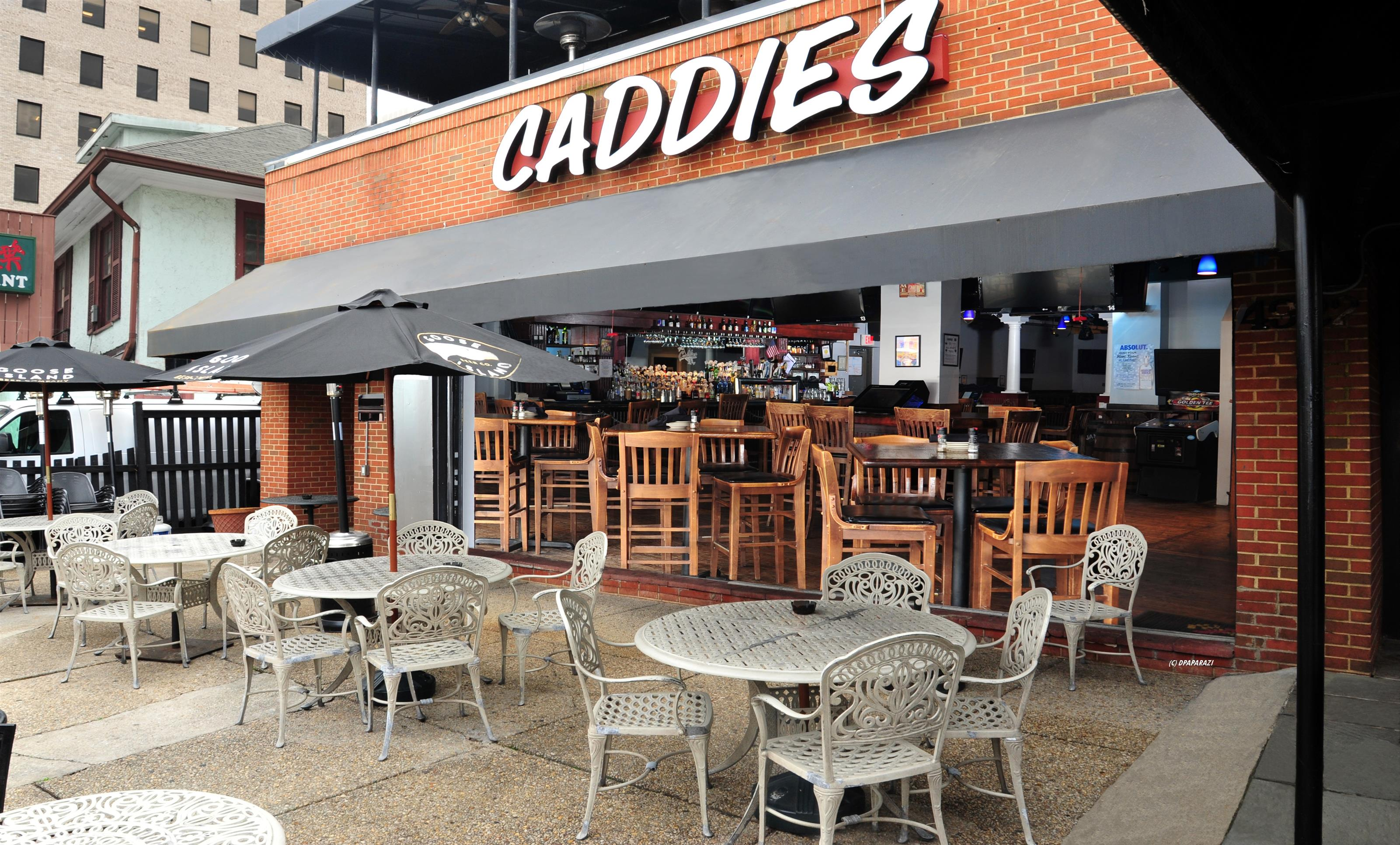 outdoor patio with tables and chairs with an open side to caddies