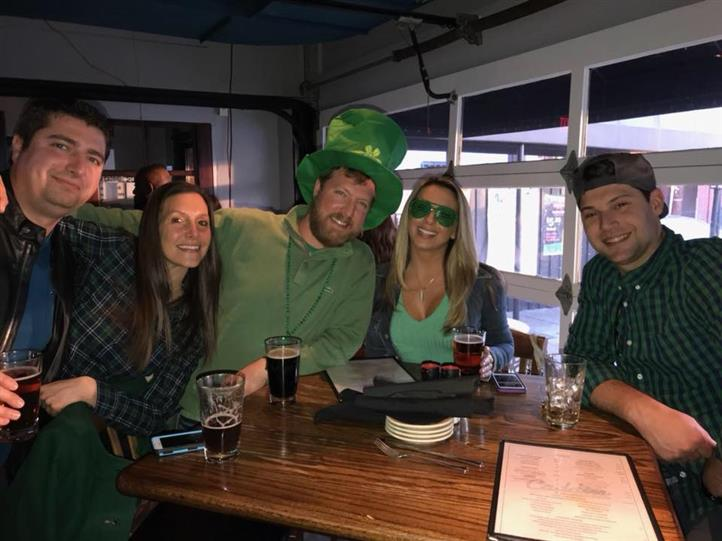 group of friends dressed up for st patricks day smiling at the camera