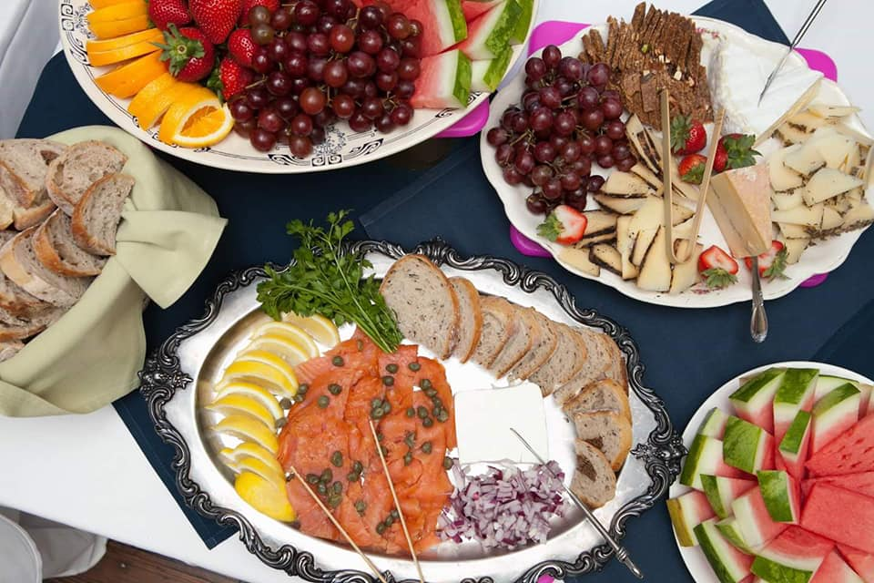 assorted platters. Fresh fruit, cheeses, and bread on a blue tablecloth.