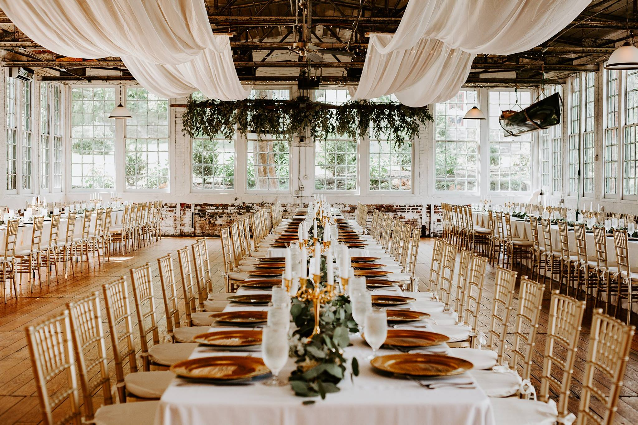 Rustic catering venue. Long white table with gold chairs, gold plates and white ceiling drapery.