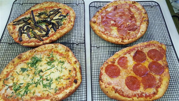 Four handmade pizzas on cooling racks. One with pepperoni, one with ham and two vegetable