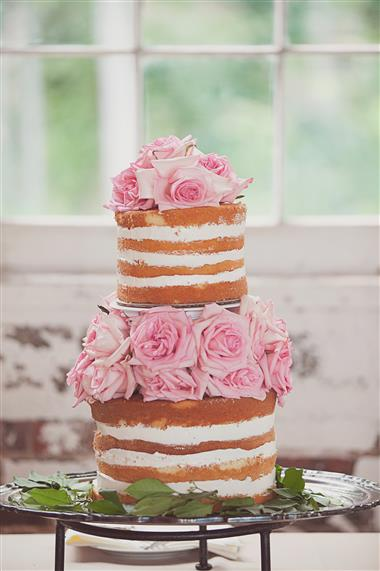 Naked wedding cake on a white table. Painted white brick wall background with farm windows.
