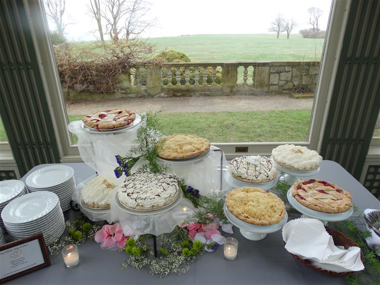 Assorted pies on a decorated table in front of the window.