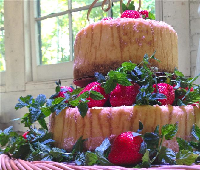 close up of a two layer cake. no icing on the cake. decorated with strawberries.