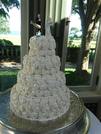 Four layer wedding cake. white icing applied to the cake in a swirl all over. bride cake topper is holding a shopping back. groom cake topper is holding his golf clubs.