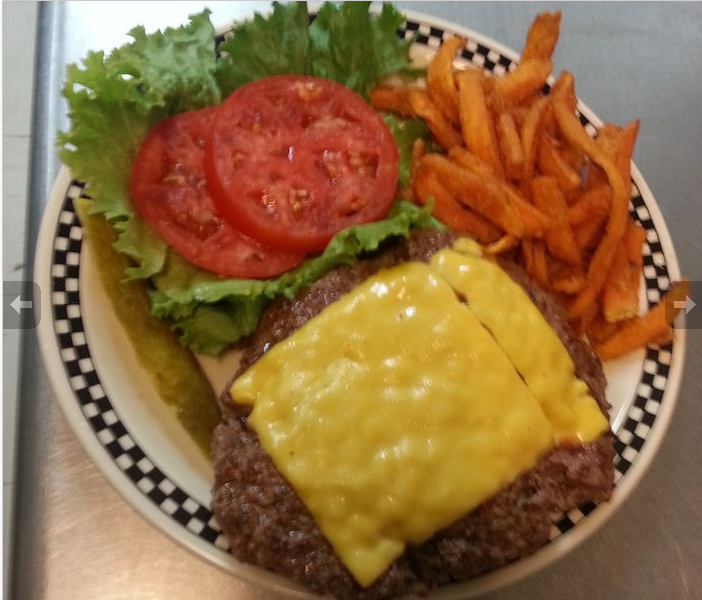 hamburger patty with a melted slice of cheese on a plate with lettuce, two tomato slices, a pickle spear and sweet potato fries