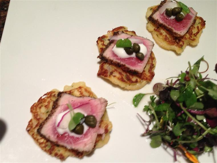 Black pepper seared ahi tuna with capers, red onions, sour cream over corn fritters with a side of micro greens.