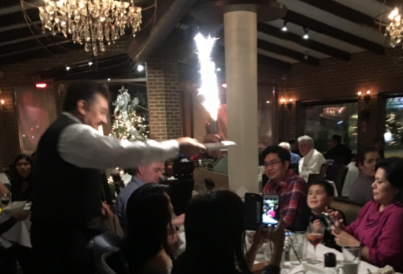 Waiter serving item with sparkler to table of people.