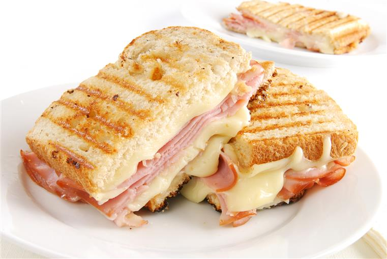 Ham and cheese sandwich on white dish.