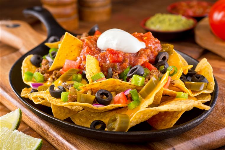 Nachos with jalapenos, black olives, salsa, sour cream on dish