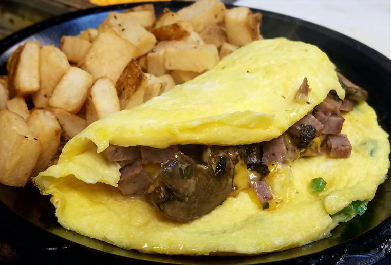 Omelete stuffed with mushrooms served wtih side potatoes