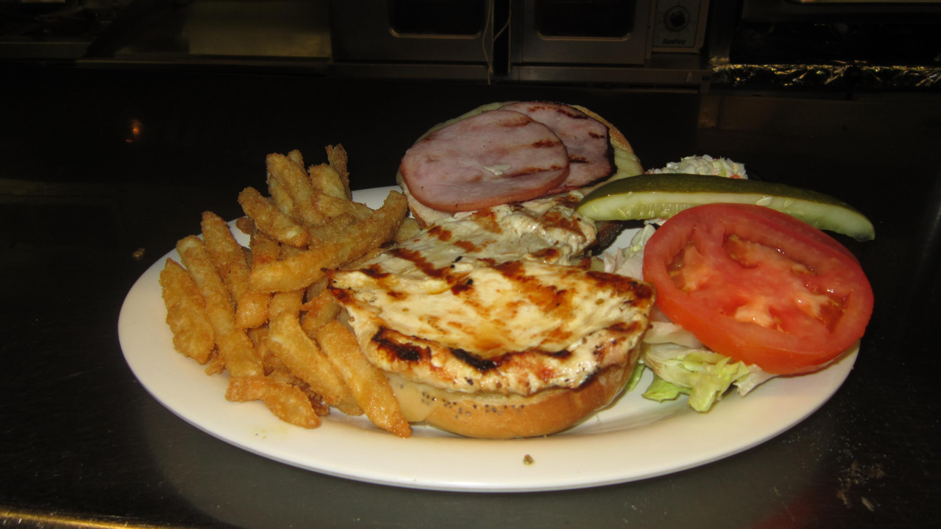 baked ham sandwich with lettuce, tomato, a pickle and fries on the side