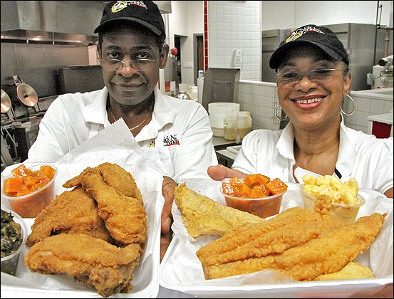 Two people holding platters of fried food and fresh sides