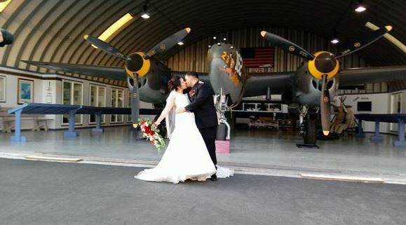 Bridge and groom kissing in front of Plane of Fame in hangar