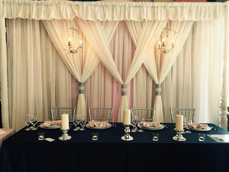 Long table with four placesettings and chairs undernearth chandelier. White curtains in background