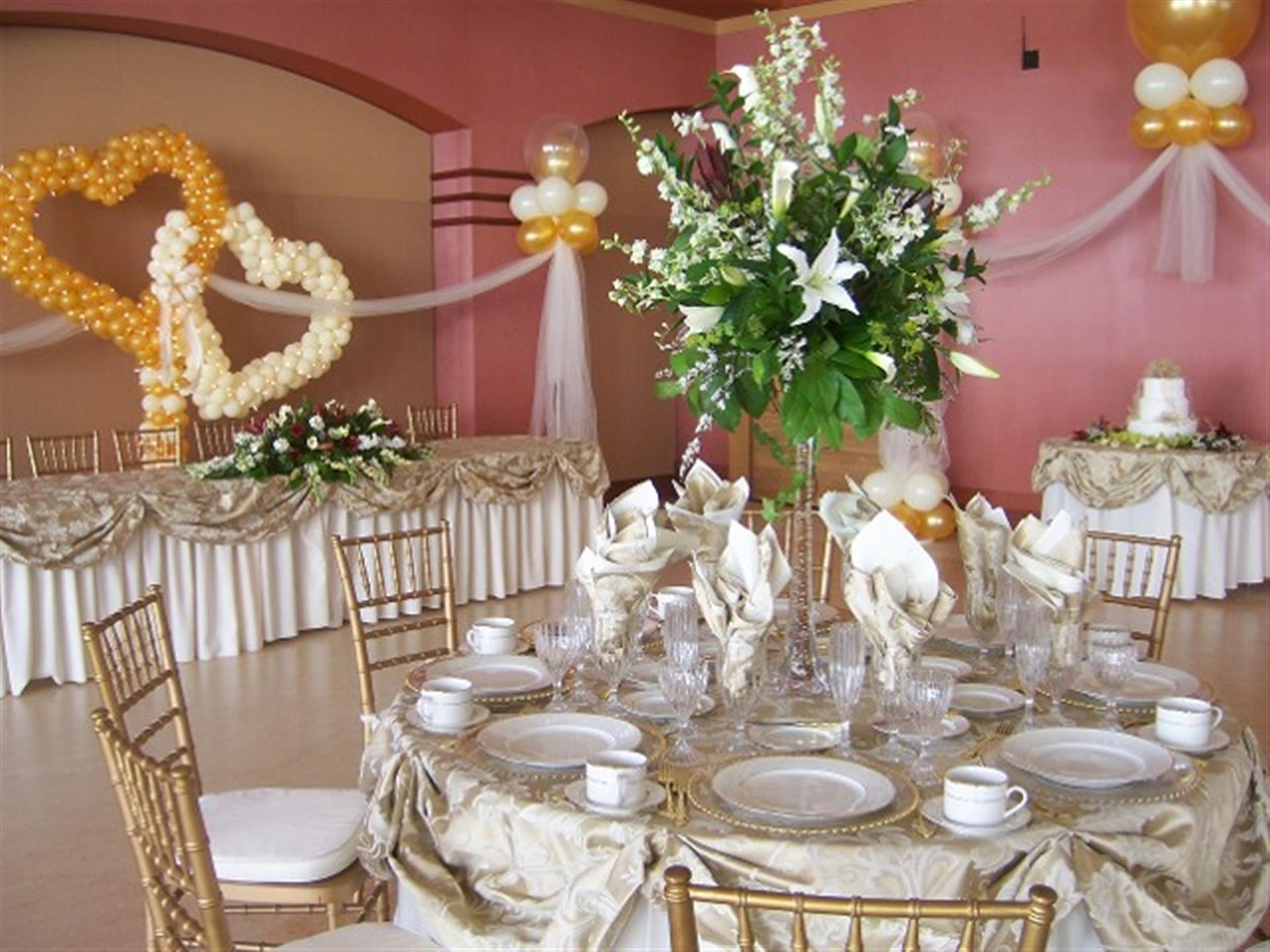 White table setting with gold chairs. Balloons of gold and white formed to make hearts.