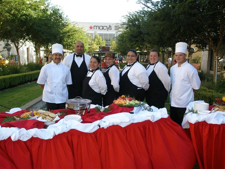 Catering staff posing for photo outdoors behind catering table
