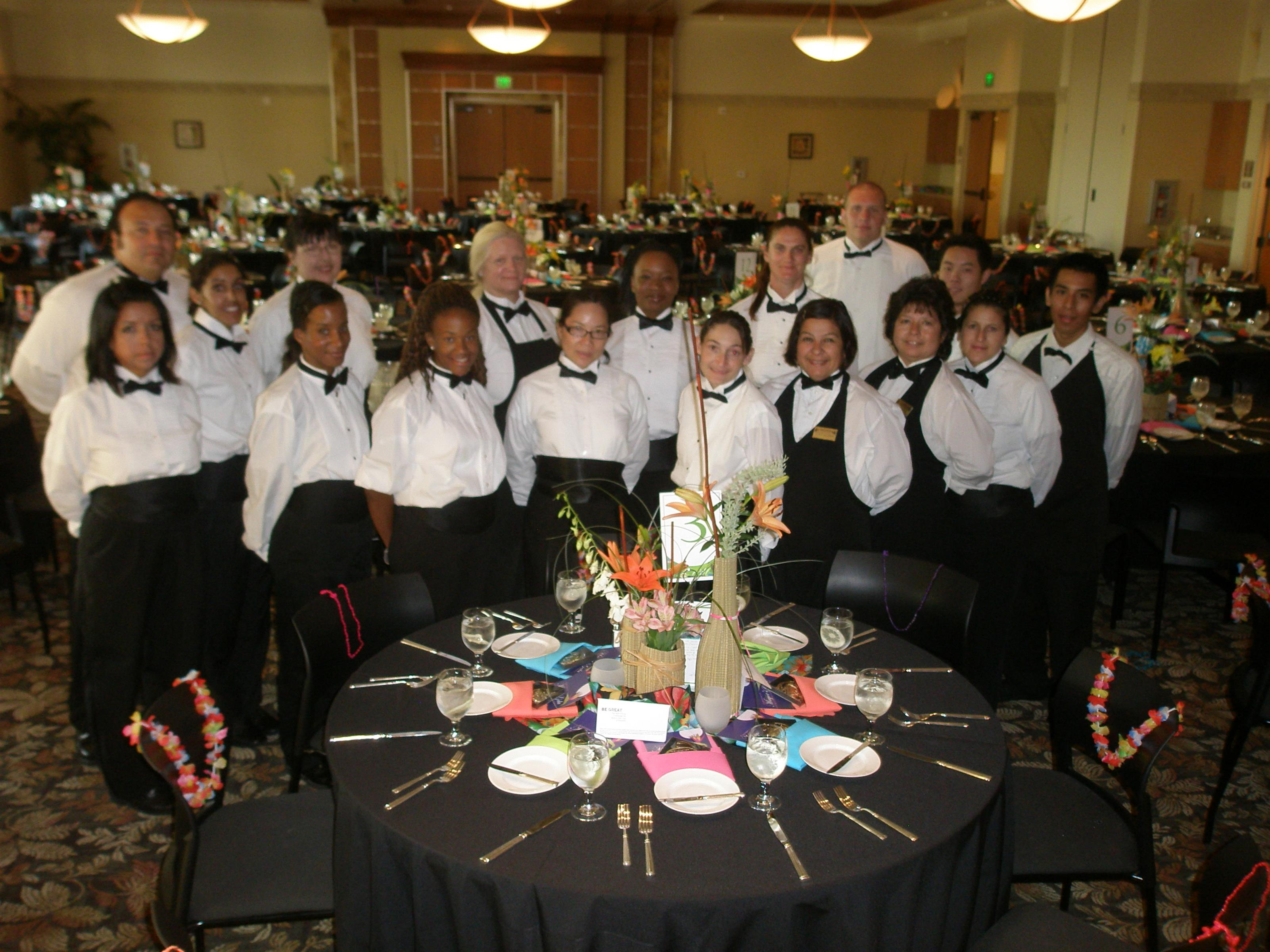 Catering staff dressed in black and white, posing behind banquet table