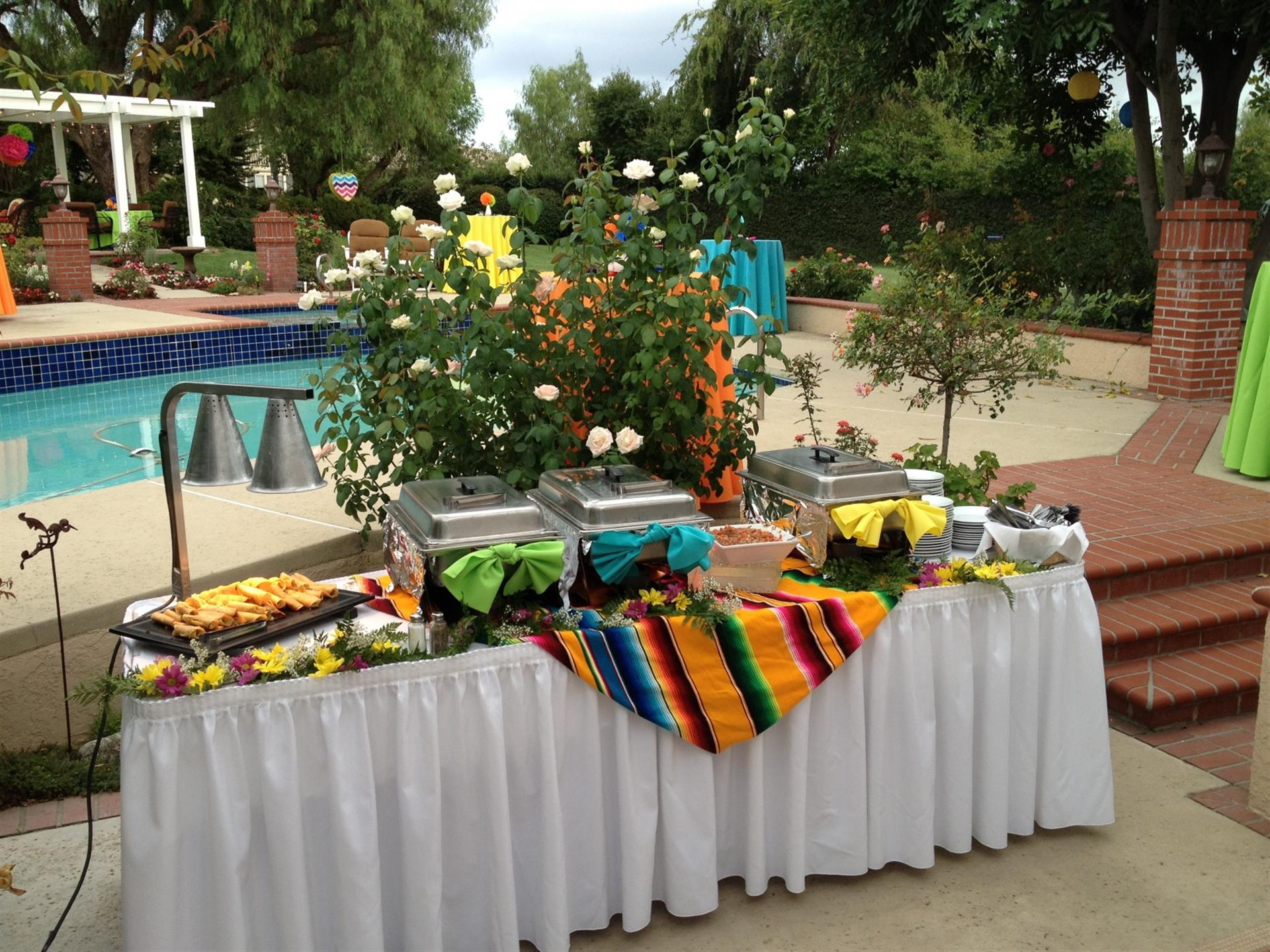 Catering table with sternos. Pool in background.