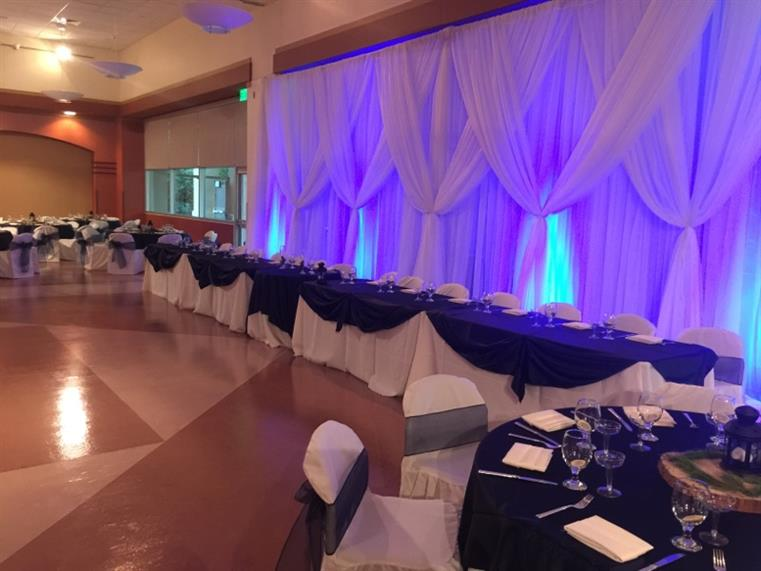 Banquet tables near wall, white curtains illuminated blue and purple