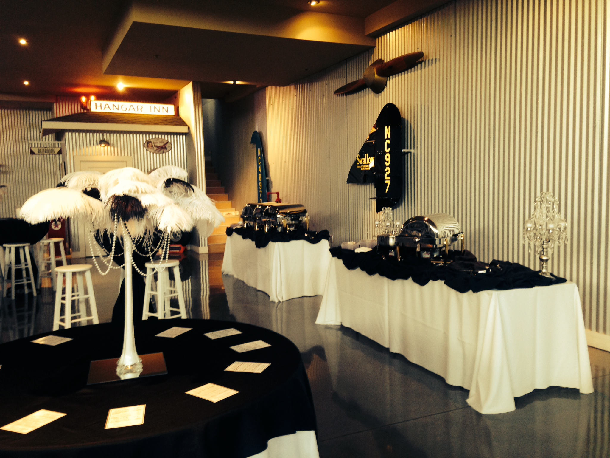 A room with white table cloths covered by black table clothes and a centerpiece of black and white feathers