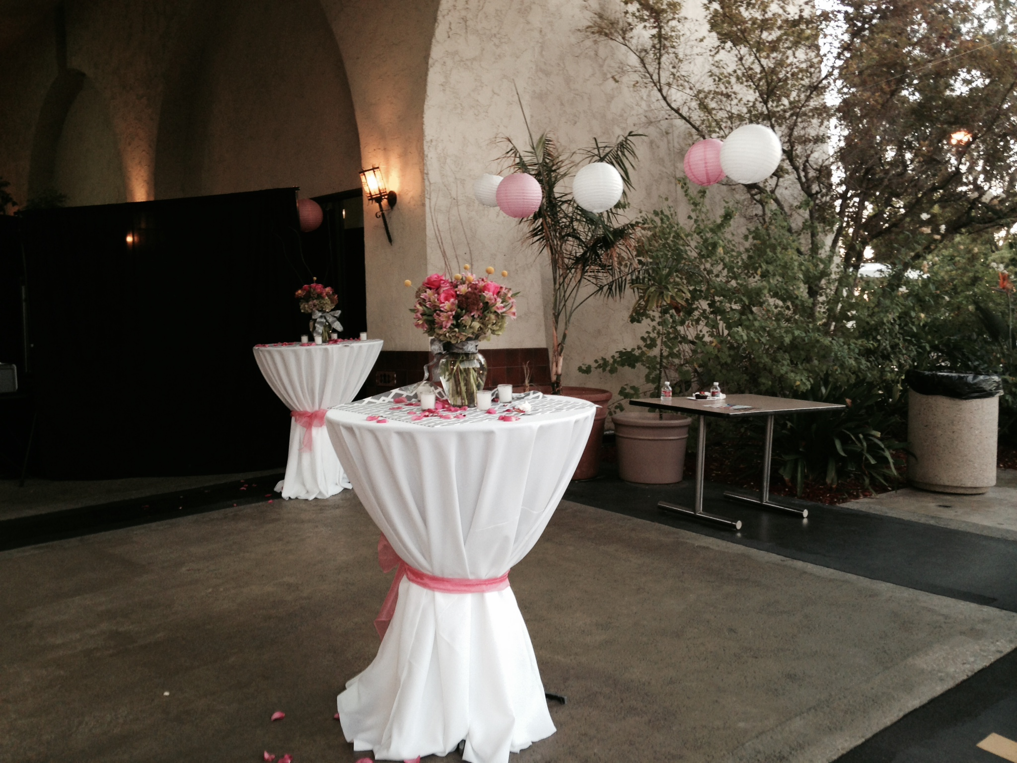 Outdoor area with two tables that are covered with white tablecloths and pink ribbons. a bouquet of flowers placed on top