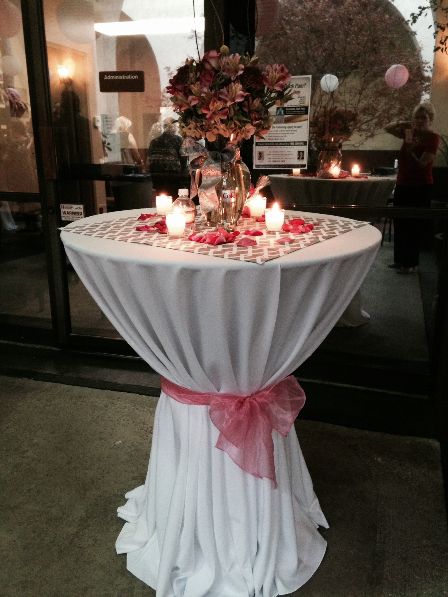 A table with a white tablecloth and pink ribbon with four lit candles on top surrounded by rose petals circling around a bouquet