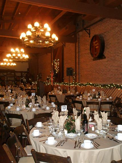 White-clothed tables with wood chairs, chandeliers, brick walled room