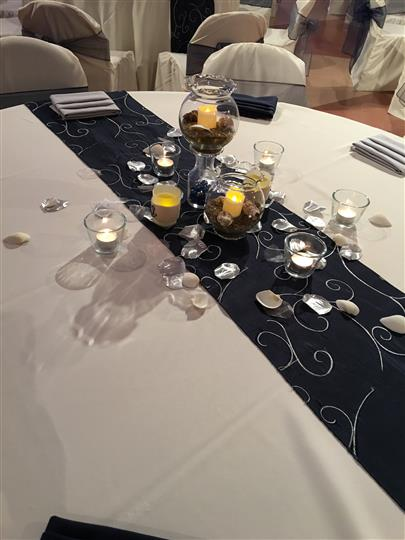 table with white tablecloth and black table runner with lit candles on top
