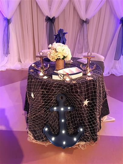 A nautical themed table with a fish net and light up anchors