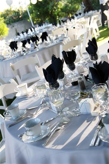 tables outdoors with white tablecloths and black napkins with place settings