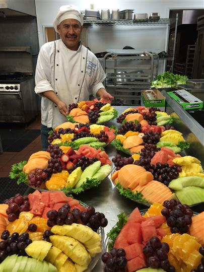 a chef with his creations of many platters of fruit for catering