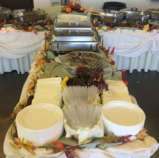 Side of a catering table where the plates, napkins and utensils are