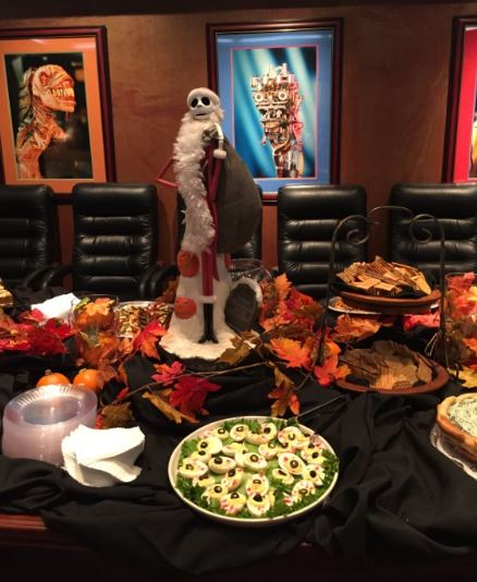 autumn-themed table with catering food on top