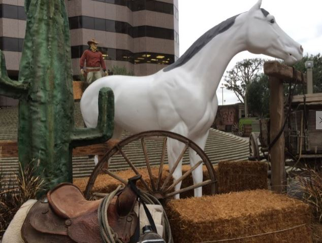 Fake white horse with hay bales, saddle, cactus on outdoor display
