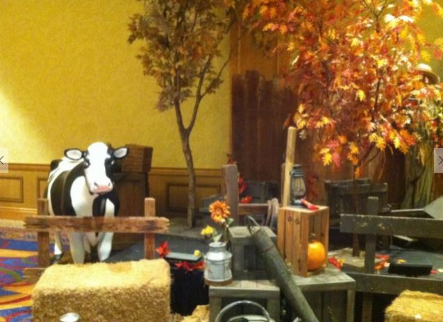 Fall display with leaves, hay bale, fake cow and farm items