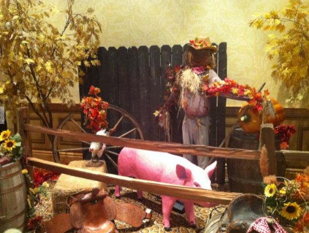 Fall display with leaves, hay bale, fake pig and scarecrow against fence