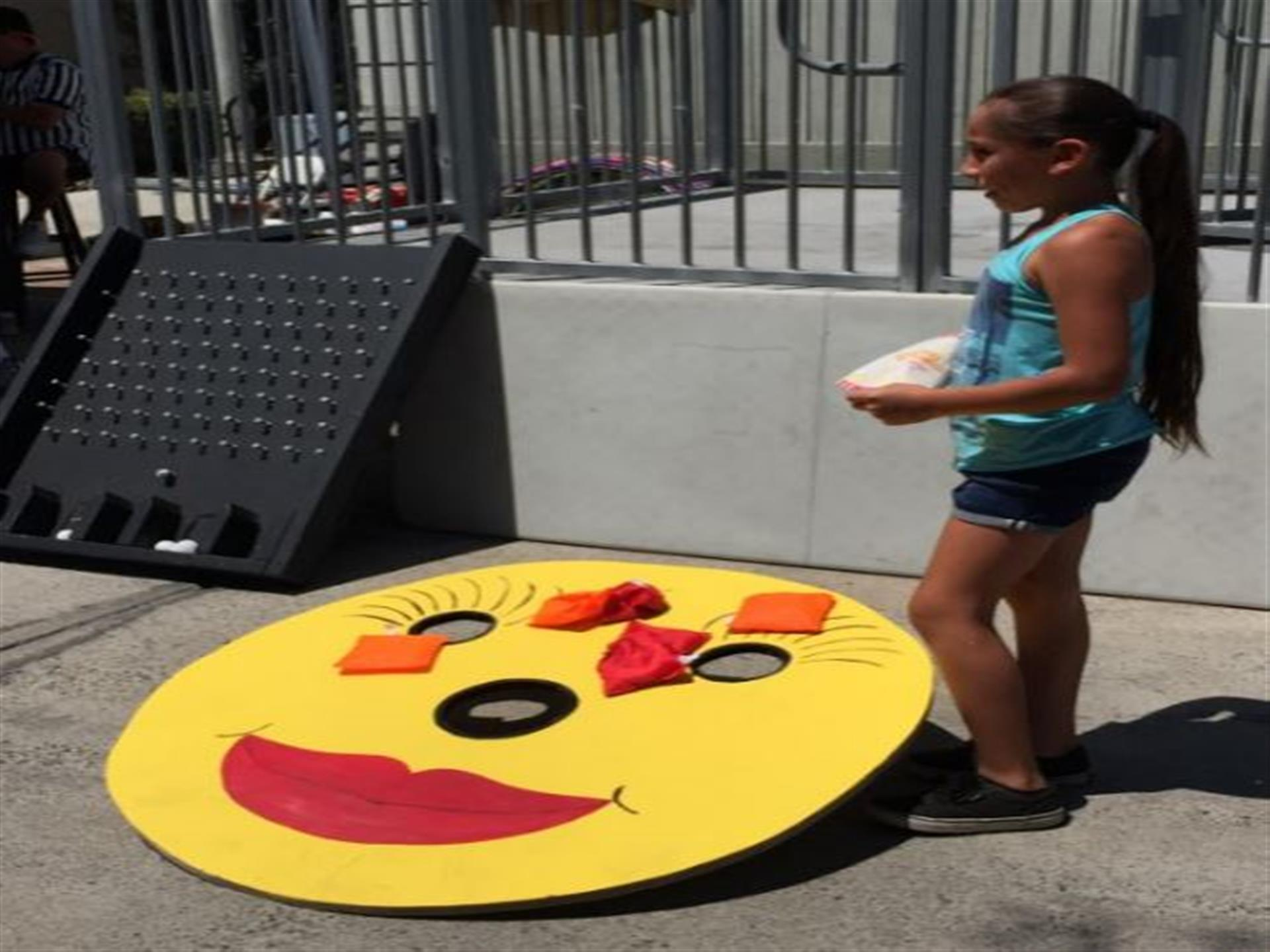 Young girl standing next to bean bag toss board