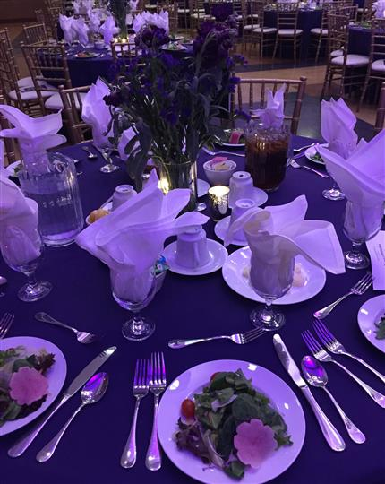a purple table cloth on a table with place settings and a plate of salad per person