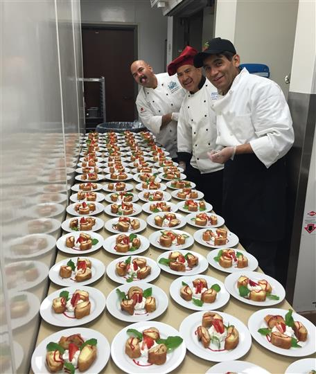 the chefs posing with many plates of dessert with strawberries