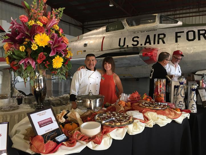 staff posing in front of a u.s. air force plane and behind a catering table with assorted desserts on top