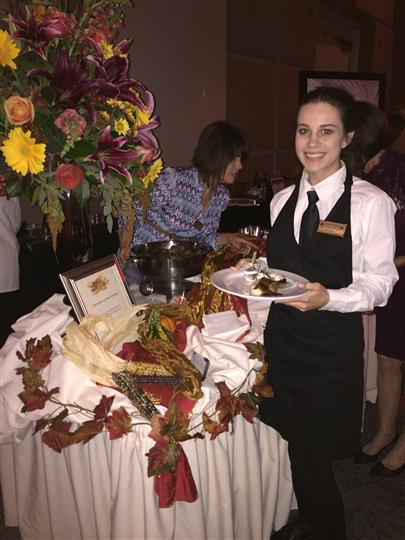 wait staff posing with plate of food in front of catering table