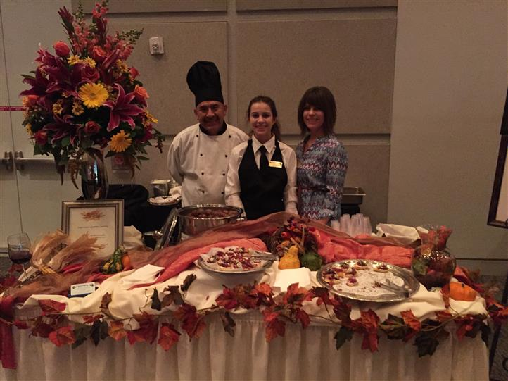 three wait staff posing behind autumn themed catering table