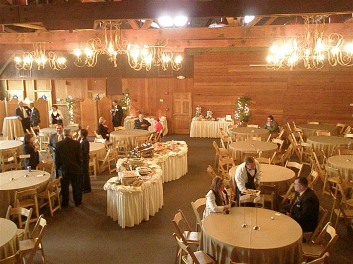 a room of tables with white tablecloths and place settings