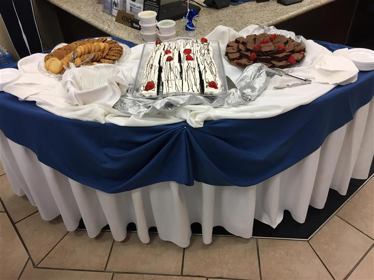 Brownies, cakes, cookies on white-clothed table with blue trim